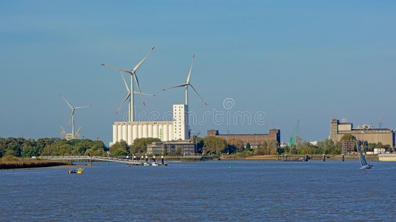 Industriebauten und Windkraftanlagen entlang einem Dock im Hafen von Antwerpen lizenzfreie stockfotos