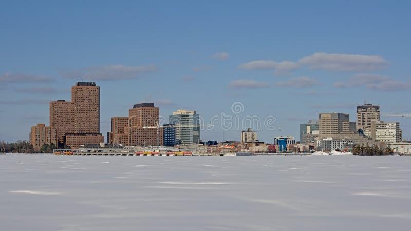 Industriebauten und Wolkenkratzer des Rumpfs entlang gefrorenem Ottawa-Fluss stockfotografie