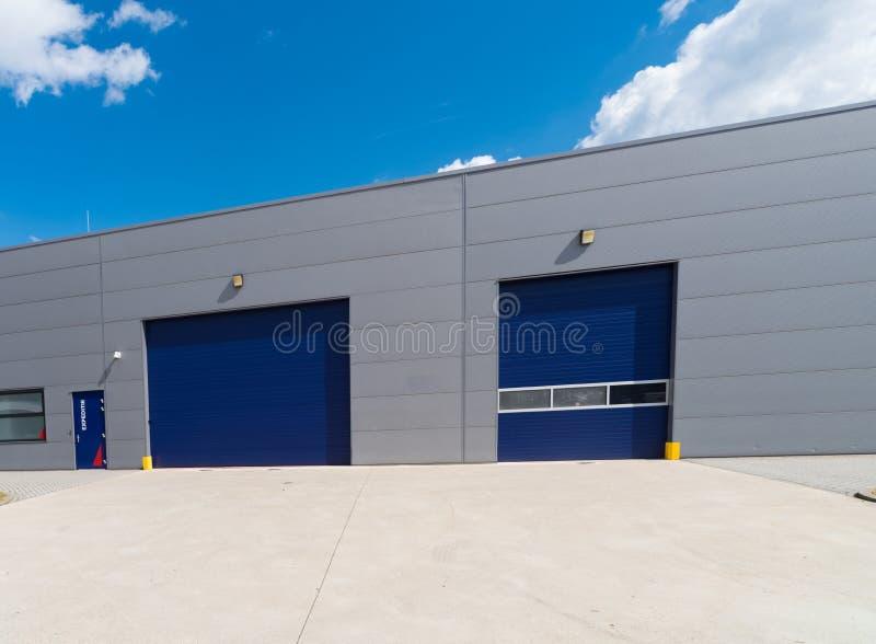 Industrieeinheit mit blauen Rollentüren stockbilder