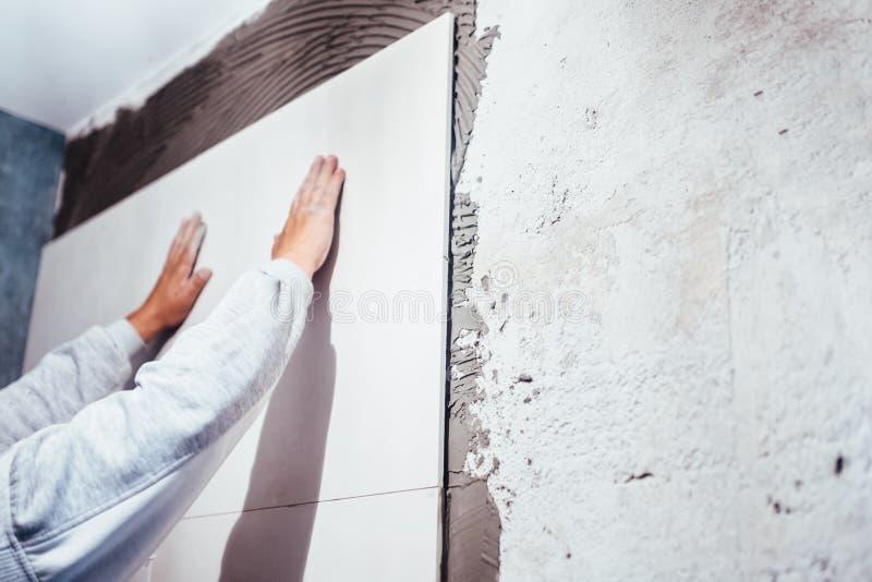 Industrieel detail, manusje van alles die grote keramische tegels installeren op badkamersmuren Douchegebied in keramische tegels stock foto's
