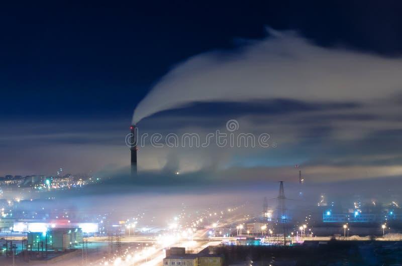 Industrieel district van de stad, de pijpen en de rook, met mist en smog bij nacht royalty-vrije stock foto