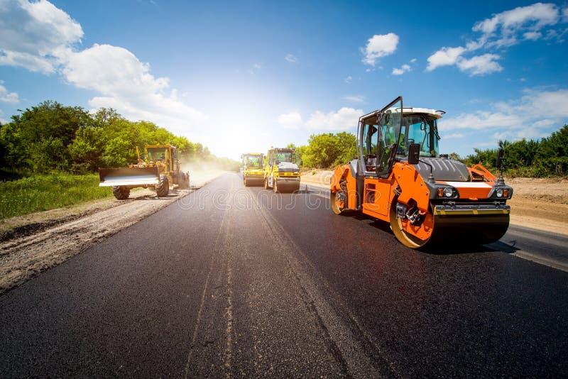 Industrieel landschap met rollen dat een nieuw asfalt in Th rolt stock foto