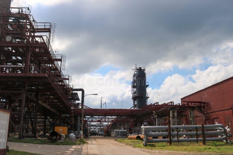 Industrieel landschap met van de pijpenmateriaal en rectificatie kolommen bij een chemische petrochemische raffinaderij industrië stock fotografie