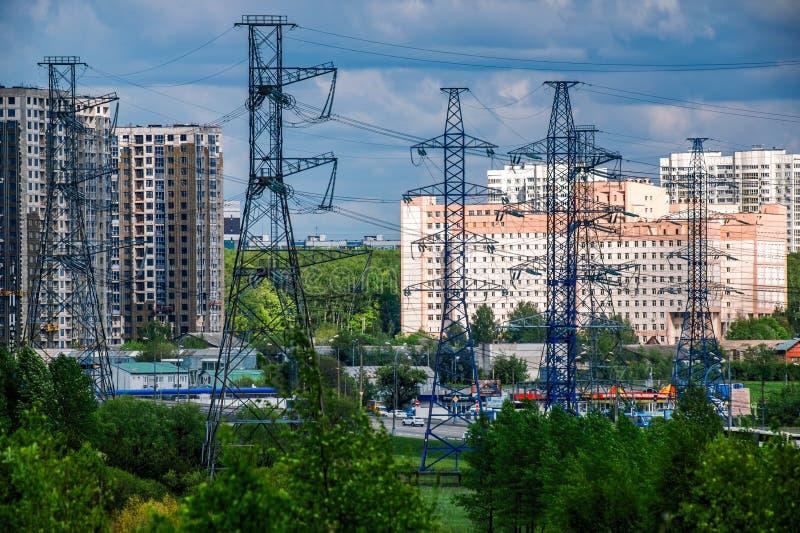Industrieel landschap Metaalsteunen van de machtslijn met hoog voltage vooraan, tegen de achtergrond, in een ijzige nevel, royalty-vrije stock fotografie