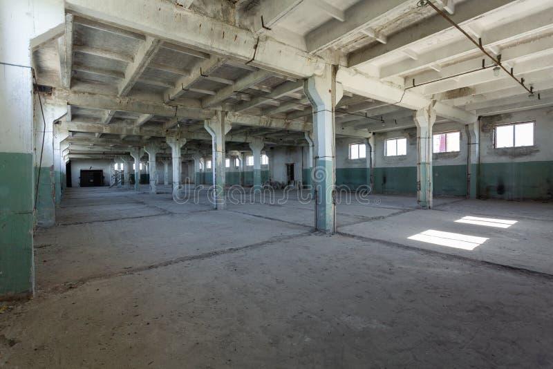 Industrieel pakhuis met cementmuren, vloeren, vensters en pijlers vóór bouw, het remodelleren, vernieuwing stock foto