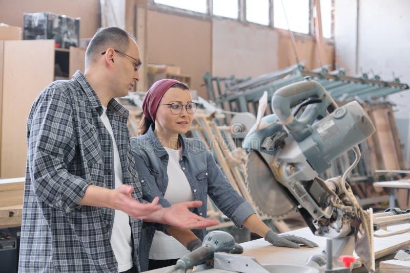 Industrieel portret die van twee werkende mannen en vrouw, bij werktuigmachines spreken stock foto