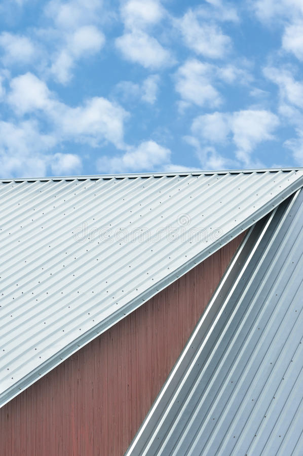 Industriegebäudedachblätter, graues Stahldachspitzenmuster, heller Sommer bewölkt cloudscape, den blauen Himmel, vertikal stockbild