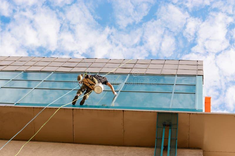 Industriekletterer, der an der Wäscheleine und an den Wäschen Windows, modernes Gebäude der Glasfassade hängt lizenzfreies stockfoto