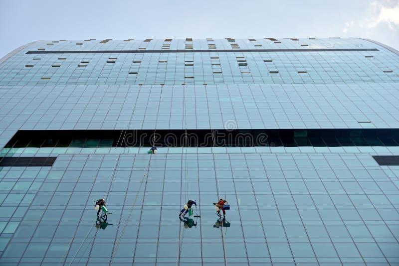 Industrieklettererwäschen Glas auf der Fassade eines Wolkenkratzers stockfoto