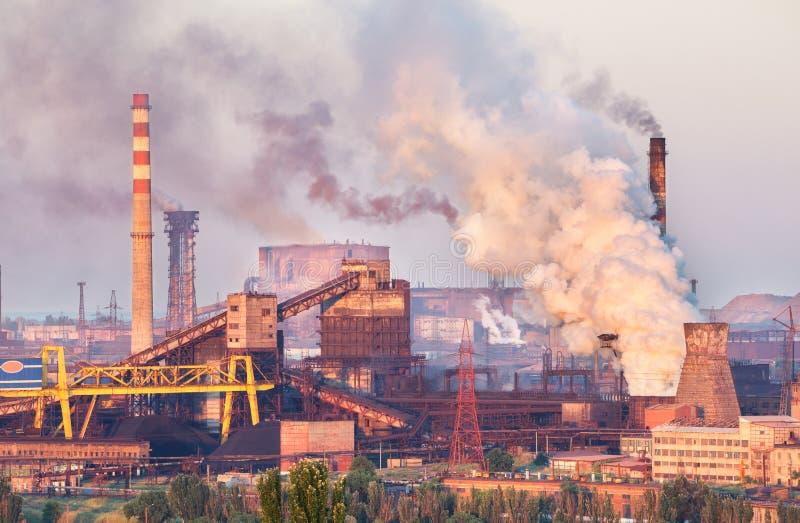 Industrielandschaft in Ukraine Stahlfabrik bei Sonnenuntergang Rohre mit Rauche Metallurgische Anlage Stahlwerk, Eisenarbeiten lizenzfreies stockfoto