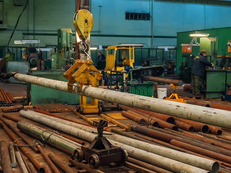 Industriell brokran som hissar stålröret i metalworking fabrik arkivfoton