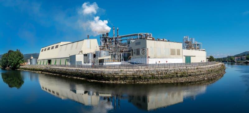 Industriell fabrik nära en flod med rör som sänder ut rök fotografering för bildbyråer