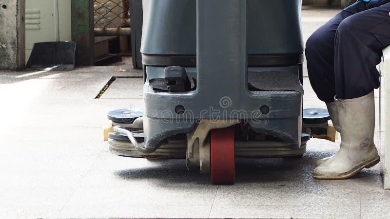 Industriell golvskurborste Skurborste för rengöra och underhållslagergolv Arbetarklädervit som väller fram kängor, sitter för sta royaltyfri fotografi