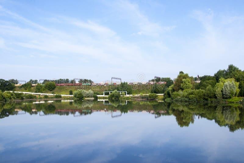 Industriell järnväg nära sjön och parkerar fotografering för bildbyråer
