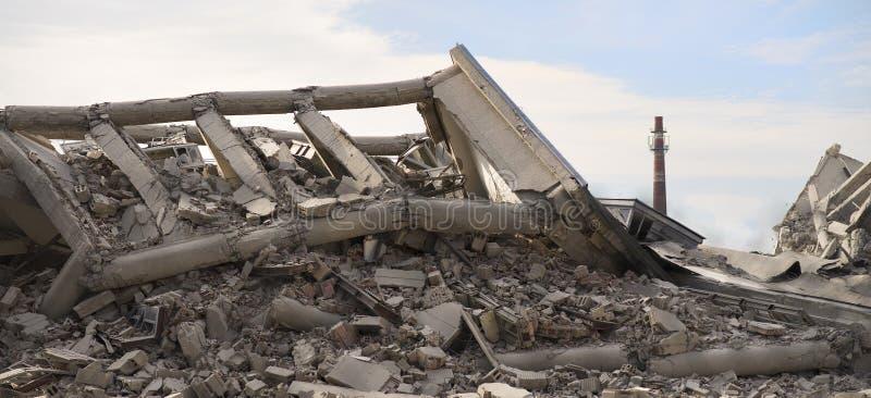 Industriell konkret byggnad destructed av slag Katastrofplats mycket av skräp, damm och kraschade byggnader royaltyfri fotografi