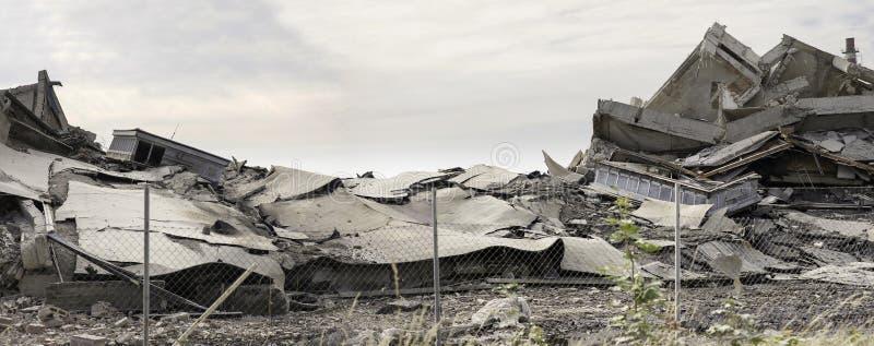 Industriell konkret byggnad destructed av slag Katastrofplats mycket av skräp, damm och kraschade byggnader arkivbilder