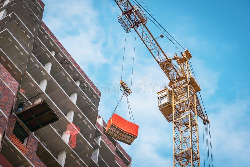 Industriell kran med last p? konstruktionsplats av ny modern bostads- byggnad arkivfoton
