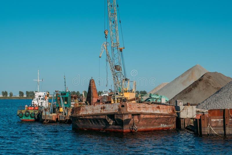 Industriell lastport med gamla skepp på floden, vattenlogistik arkivbild