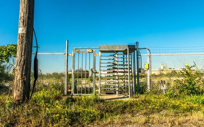 Industriell metallport med vändkors, övergiven lott i backgroun royaltyfri fotografi