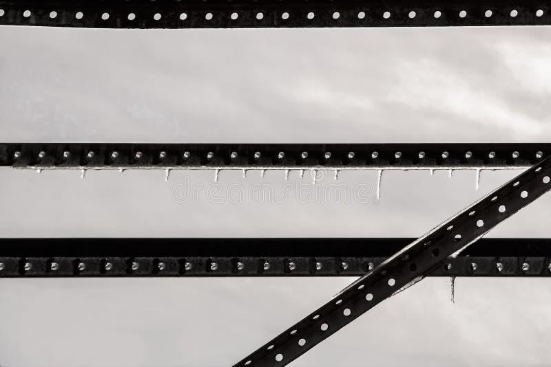 Industriell nästan abstrakt låg mättandebakgrund av fullständiga metallremsor med hål mot grå himmel med att hänga för istappar royaltyfri foto