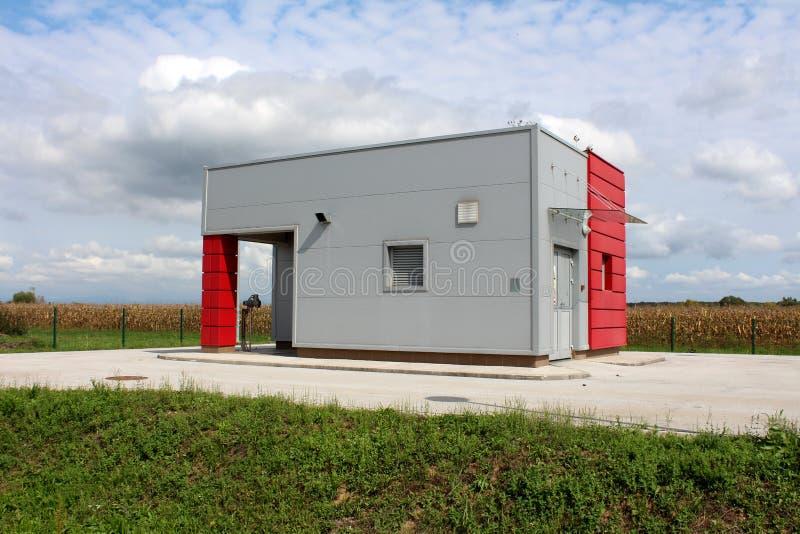 Industriell pumpa station för vatten inom den konkreta strukturen med metallväggar som omges med asfalt och gräs med cornfielden  royaltyfri fotografi