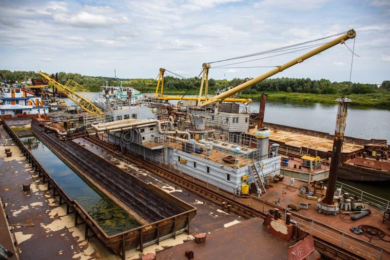 Industriell sändningsport med skepp och fartyg på floden, nautiskt logistiska skytteltrans. och bransch arkivbild