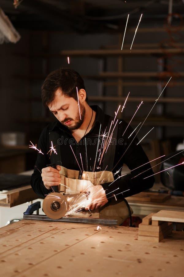 Industriell snickarearbetare som klipper metall med m?nga skarpa gnistor p? en arbetsb?nk i ett snickeriseminarium Valfokus till arkivfoto