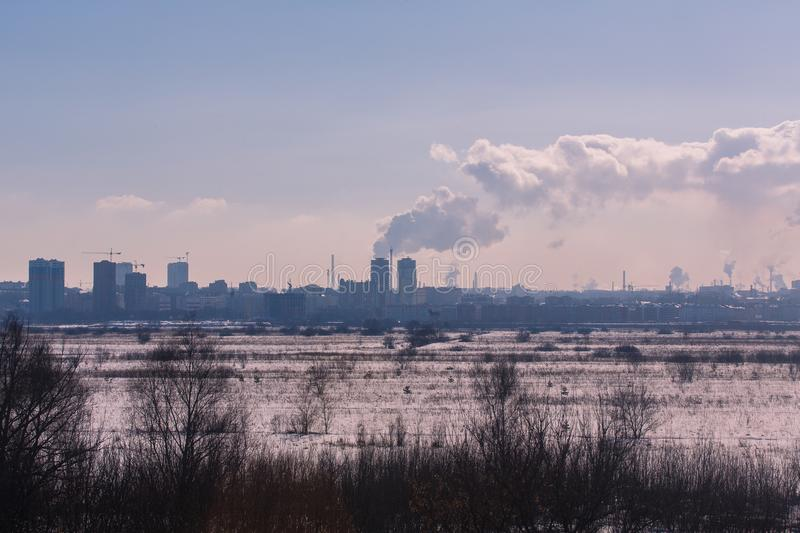 Industriell utkant för vinterlandskap av staden Konturer av byggnader och kranar royaltyfri foto