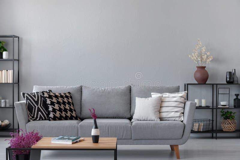 Industriell vardagsrum med den enkla gråa soffan med kopieringsutrymme på väggen royaltyfri bild