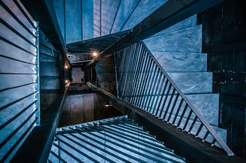 Industriell vindspiraltrappuppgång med det konkreta golvet, svart meta fotografering för bildbyråer