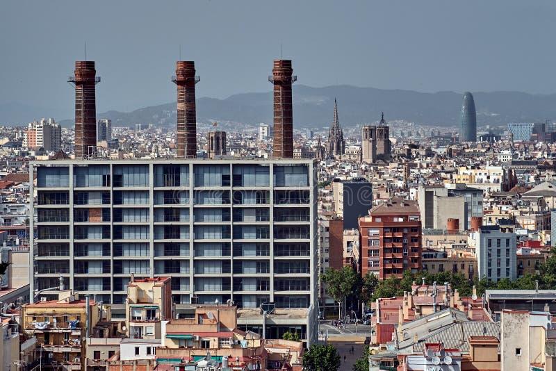 Industriella Barcelona Tre lampglasrör för röd tegelsten med historiska Barcelona på bakgrund royaltyfri bild