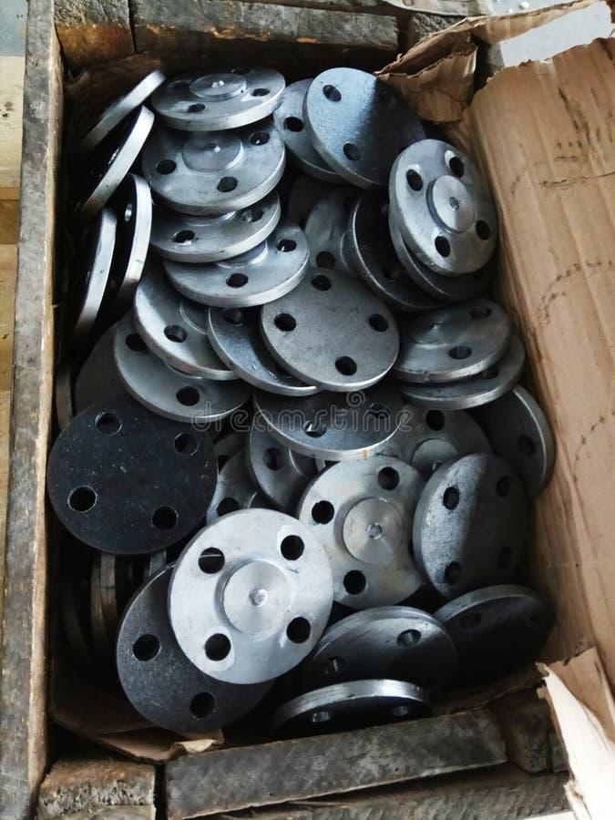 industriella delar som snidas från skinande metall, sprids i en ask royaltyfria bilder