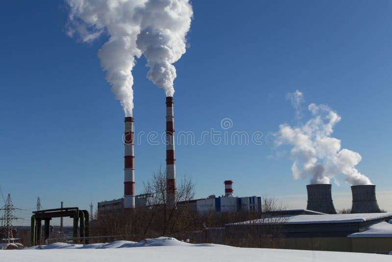 Industriella fabriksrör med rök royaltyfri bild