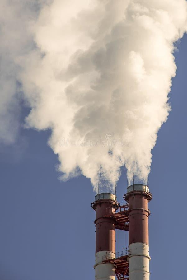 Industriella fabriksrör röker på solen på blå himmel Ekologiproblem arkivfoto