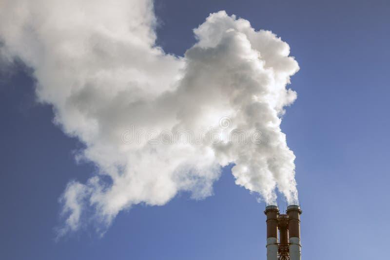 Industriella fabriksrör röker på solen på blå himmel Ekologiproblem royaltyfria foton