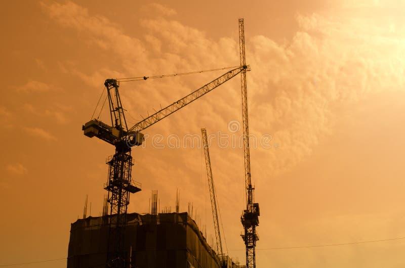 Industriella konstruktionskranar och byggnadskonturer över solen royaltyfria foton