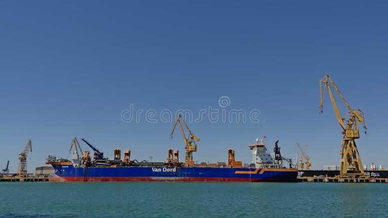 Industriella kranar längs en frieghter i hamnen av Cadiz arkivbilder