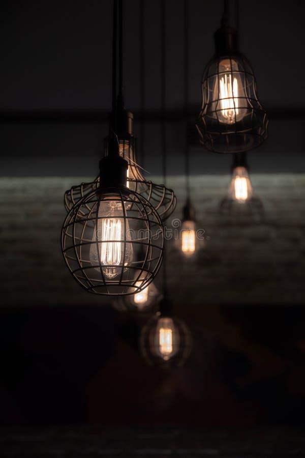 Industriella stiltrådlampor med glödtrådar som glöder inom ljusa kulor för exponeringsglas i mörker Skinande ljus och mörk bakgru arkivfoton