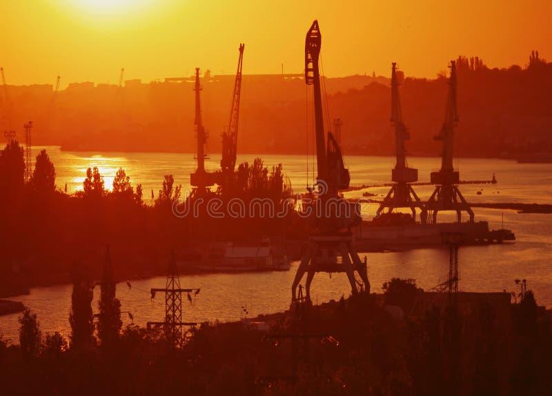 Industrielle Flusshafenlandschaft mit Kränen auf einem Fluss stockfoto