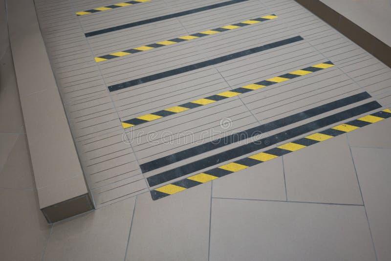 Industrielle gestreifte Straßen- oder Schrittwarnung auf grauer Rampe für handica lizenzfreie stockbilder