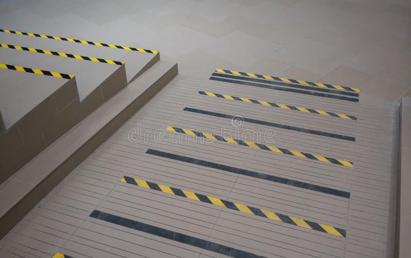 Industrielle gestreifte Straßen- oder Schrittwarnung auf grauer Rampe für handica lizenzfreie abbildung