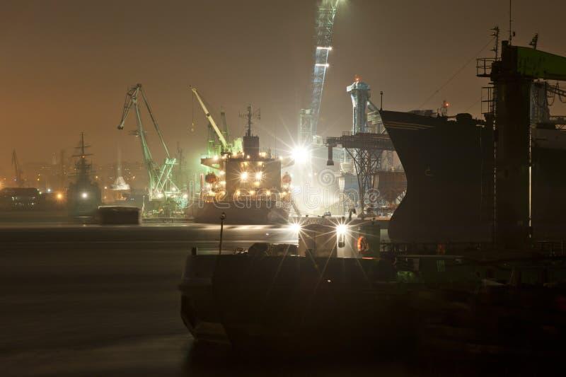 Industrielle Hafennachtansicht und Frachtschiff stockbilder