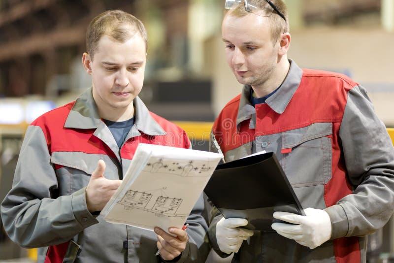 Industrielle Herstellungsarbeitskräfte, die technische Konstruktionszeichnung lesen lizenzfreie stockbilder