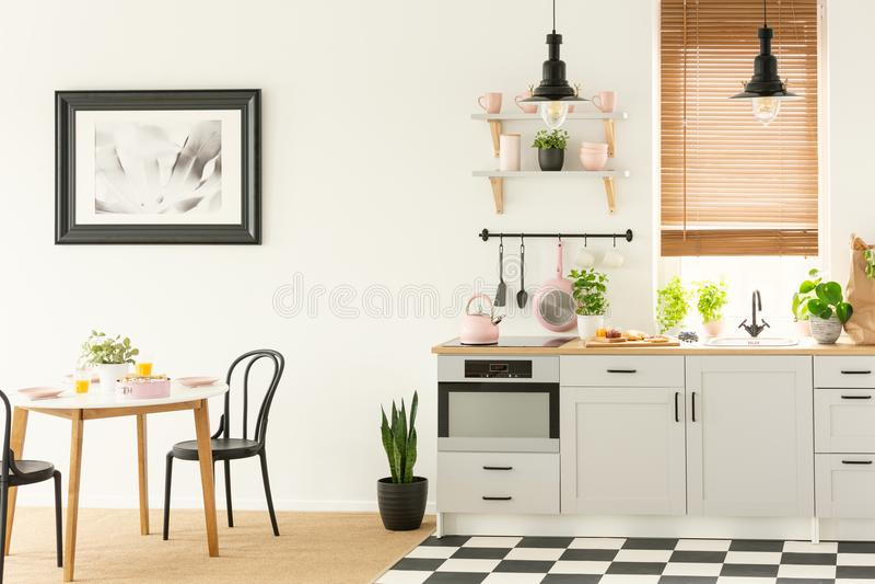 Industrielle Lampen und Schwarzes, die Stühle in einem weißen Kücheninnenraum mit einem modernen Ofen und einer Frühstücksnahrung stockfoto