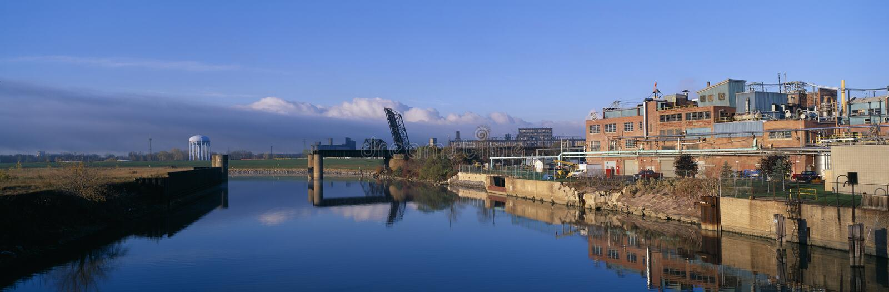 Industrielle Landschaft entlang kranke Pflanzen entferntem Fluss stockbild