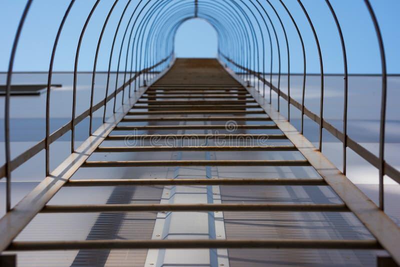 Industrielle Leiter auf der Fassade des Gebäudes, das zum Himmel steigt stockfoto