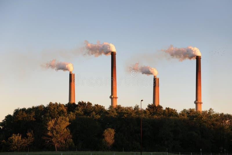 Industrielle Smokestacks am Sonnenuntergang stockbilder
