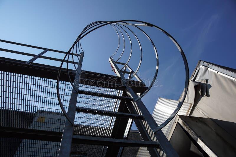 Industrielle vertikale Treppe mit klarem skybackground Vertikale Treppe des Gebäudes Stahlleiter mit Schutz lizenzfreies stockbild