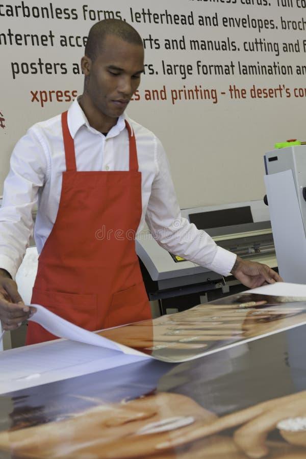 Industrieller Arbeiter, der in der Druckmaschine arbeitet stockbild
