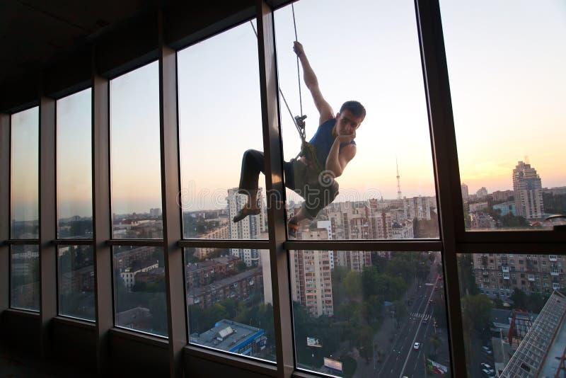 Industrieller Bergsteiger, der durch ein Fenster schaut lizenzfreies stockbild